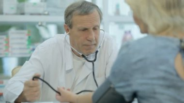 The doctor measures the pressure of a woman in a drugstore — Vídeo de stock