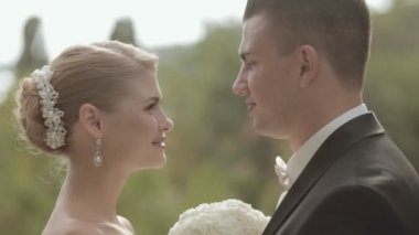 Young newlyweds looking at each other with love and kisses — Stock Video