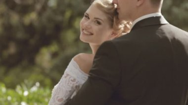 The groom embraces fiancee standing in a park — Stock Video