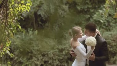 Groom and bride in a beautiful dress kissing in the park — Stockvideo
