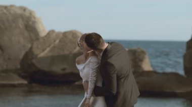 Happy newlyweds dancing on the seaside near cliffs — Stock Video