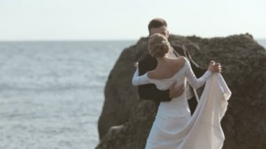 Sweethearts newlyweds dancing on the seaside near cliffs — Stockvideo
