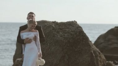 Laughing newlyweds dancing on the seaside near cliffs — Stock Video