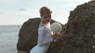 Beautiful bride with bouquet posing at the rock near the sea — Stock Video