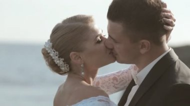 Close-up of kissing newlyweds standing among the rocks near the sea — Stockvideo
