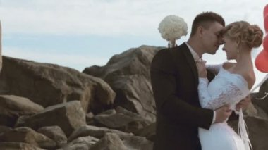 Adorable bride and groom stand with balloons in the form of heart in the rocks by the sea — Stock Video