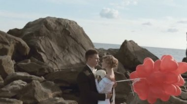 Beautiful newlyweds stand with balloons in the form of heart in the rocks by the sea — Stock Video