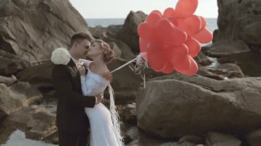 Enamoured newlyweds stand with balloons in the form of heart in the rocks by the sea — Stock Video