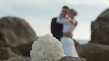 Bridal bouquet and newlyweds in love out of a focus — Stock Video