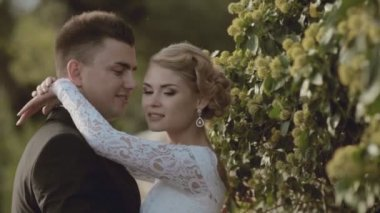 Happy newlyweds standing in the greenery — Stock Video