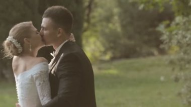 Young bride and groom kissing and laughing in green park — Stock Video