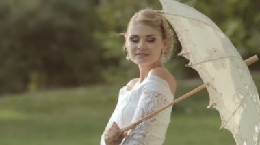 Shapely bride posing with an umbrella on the nature — Video Stock