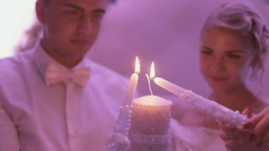 Newlyweds holding the burning candle — Stock Video
