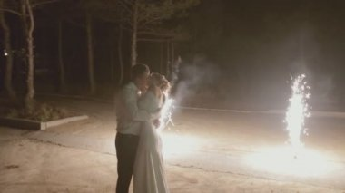 Newlyweds kissing under the fireworks in the street — Stock Video