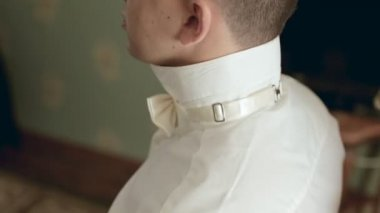 Young stylish groom puts bow-tie on shirt — Stock Video