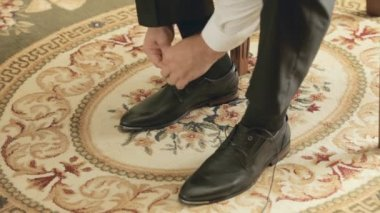 The groom puting shoes on and ties shoelaces — Stock Video