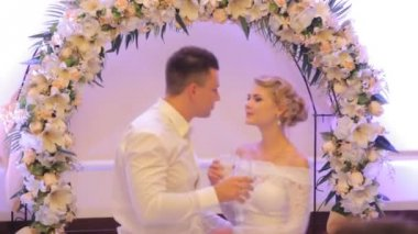 Bride and groom kissing in a restaurant while standing under flower arch — Stock Video