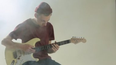 Guy in hat playing guitar in the studio in smoke — Stock Video