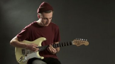 Pensive guitarist playing guitar in a dark studio — Stock Video