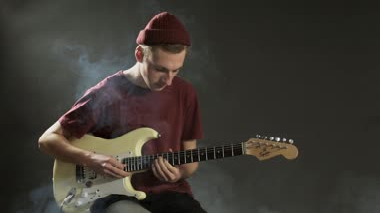Thoughtful guitarist playing guitar in dark studio — Stock Video