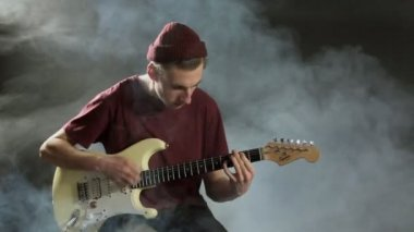 Young guy playing guitar in a dark studio in smoke — Stock Video