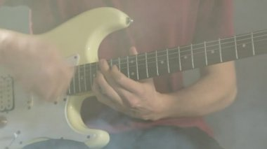 Close-up of a young man playing guitar in a dark studio in smoke — Stock Video