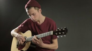 Young musician playing guitar in dark studio — Stock Video