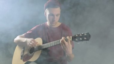 Talented young musician playing guitar in a dark studio in smoke — Stock Video