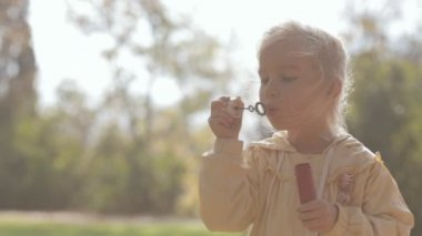 Little blonde girl blow bubbles on nature — Stock Video