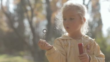 Close up of a little blonde girl blow bubbles on nature — Stock Video