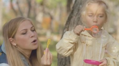 Mom and daughter blow bubbles in the park — Wideo stockowe