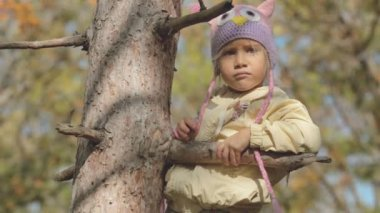 Little girl in a hat-owl sits on a tree in the park — Vidéo