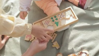 Little children collect wooden toy with numbers — Stockvideo