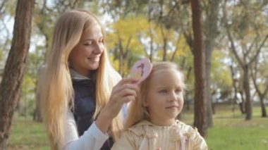Mom combing hair of little cute daughter on nature — Stock Video