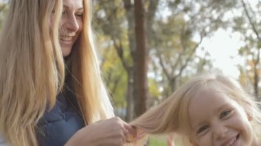 Mom combing long blond hair of daughter on nature and laughing — Video Stock