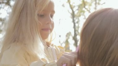 Close up of little girl combing long blond hair of her mother on nature — Stock Video