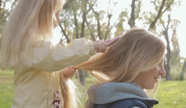 Little girl combing long hair of her mother on nature — Stock Video