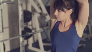 Girl in sportswear doing stretching in a fitness room among  exercise machines — Vídeo de Stock