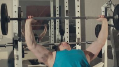 Bodybuilder in the exercise machine  build muscles with a barbell — Stock Video