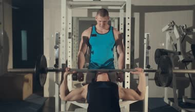 Man training with personal trainer at the gym, pumping iron — Vídeo de stock