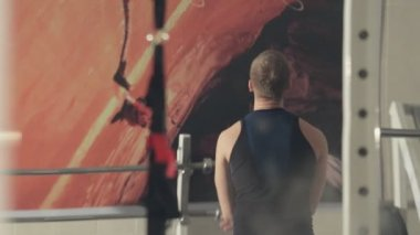 Man does warm up before exercise in the gym, rear view — 图库视频影像