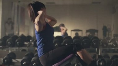 Beautiful young woman doing abdominal exercises on exercise machine in the gym in front of mirror — Stock Video
