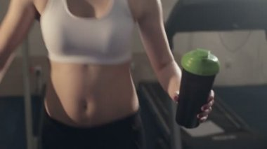 Girl goes on a treadmill and drinking water — Stock Video