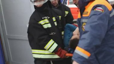 Sevastopol, Crimea, Russia - March 26, 2015: Firefighter exercises. Lifeguards save man, put him on a stretcher and evacuate him. Doctor provides first aid — Stock Video