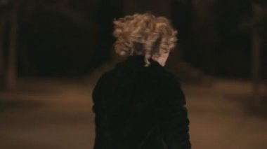 The girl in a fur coat, short dress and heels walking along a dark park,then begins to run — Video Stock