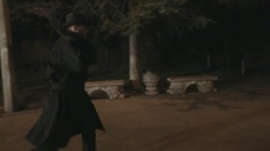 Man in a black cloak and hat runs through the park at night for someone — Stock Video