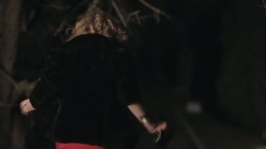 Beautifully dressed woman runs away from someone in the park at night — Stock Video