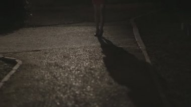 Shadow and the girls legs in high heels standing in the dark park alone at night — Stock Video