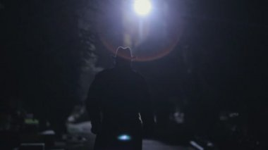 Suspicious man in a black cloak and hat going at night in the park — Stock Video