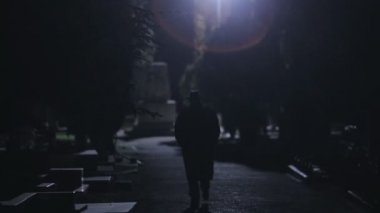 Mysterious man in black cloak and hat going at night in the park — Stock Video